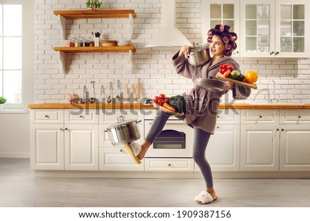 Tired housewife cooking food and carrying lots of stuff. Frail slim young woman making meal at home, holding multiple heavy cooking pots and kitchen saucepans, balancing cutting boards with vegetables Royalty-Free Stock Photo #1909387156
