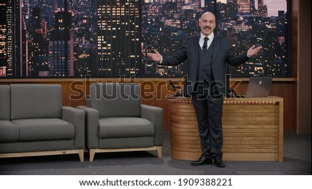 Late-night talk show host is performing his monologue, looking into camera. TV broadcast style show.  Royalty-Free Stock Photo #1909388221