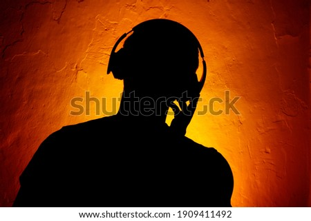 A silhouette of a man wearing headphones, on a textured wall background.