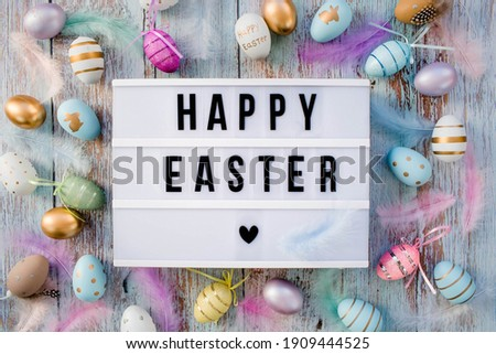 Stylish text frame of the lightbox with the inscription happy easter. Pink, blue, white, gold, and yellow eggs are everywhere. Colorful Easter eggs top view. Copyspace. Royalty-Free Stock Photo #1909444525