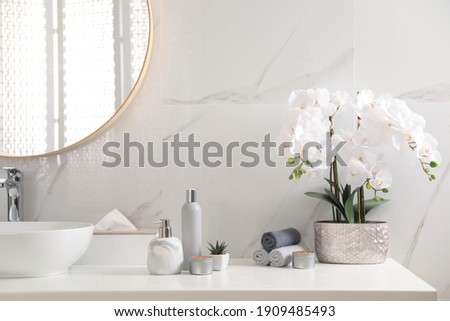 Beautiful flowers, burning candles and different toiletries on countertop in bathroom Royalty-Free Stock Photo #1909485493