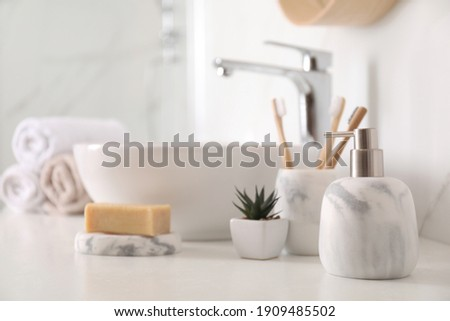 Holder with toothbrushes, plant and different toiletries near vessel sink in bathroom Royalty-Free Stock Photo #1909485502