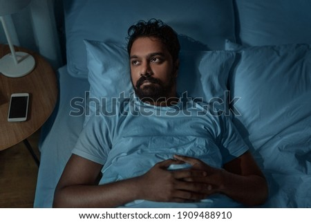 sleeping, insomnia and people concept - speelpess indian man lying in bed at home at night Royalty-Free Stock Photo #1909488910