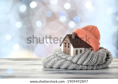 Figure of house and warm clothes on table against blurred lights. Concept of heating season Royalty-Free Stock Photo #1909492897