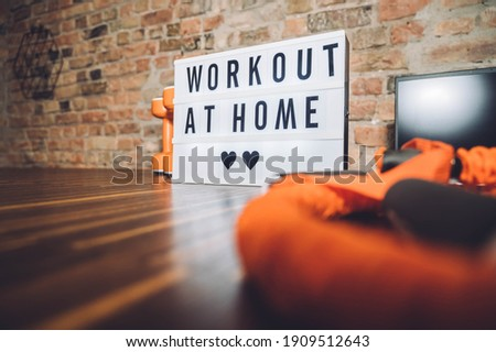 Sport equipment and lightbox with text WORKOUT AT HOME on the floor indoors. Message to promote self-isolation during COVID‑19 pandemic. Working out at home.