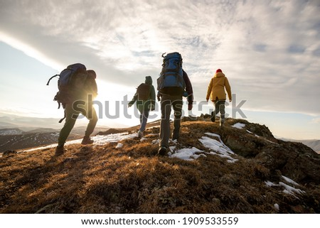 Group of four hikers with backpacks walks in mountains at sunset Royalty-Free Stock Photo #1909533559
