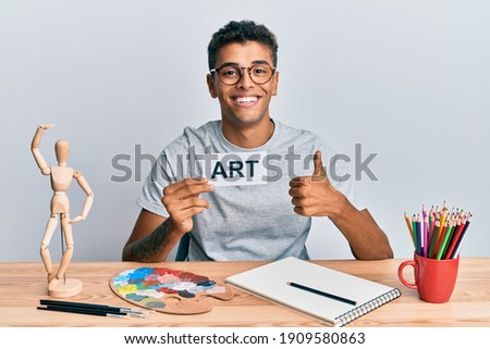 Young handsome african american man painter sitting at art studio holding art word smiling happy and positive, thumb up doing excellent and approval sign