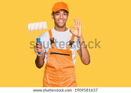 Young handsome african american man wearing cap and painter clothes holding painting roll doing ok sign with fingers, smiling friendly gesturing excellent symbol