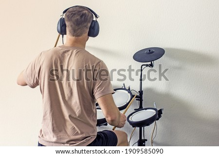 A man without a face in a light T-shirt with headphones and drumsticks playing an electronic drum kit at home, rear view. Home art hobbies authentic concept. Musical hobby drums Royalty-Free Stock Photo #1909585090