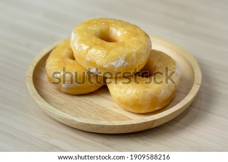 Tasty original icing sugar donuts served on wooden plate. Bakery food close-up photo. Royalty-Free Stock Photo #1909588216