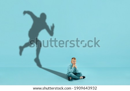 Childhood and dream about big and famous future. Conceptual image with boy and shadow of sportive male runner, champion on blue background. Childhood, dreams, imagination, education concept. Royalty-Free Stock Photo #1909643932