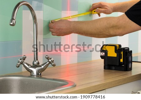 A professional checks the angles while taking measurements of the kitchen Royalty-Free Stock Photo #1909778416