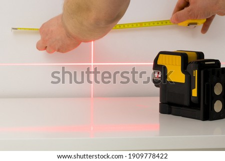 Electronic laser for checking angles and straight lines during measurements Royalty-Free Stock Photo #1909778422