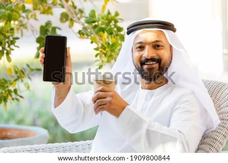 Middle Eastern Arab Emirati man at the Cafe in Dubai, United Arab Emirates Royalty-Free Stock Photo #1909800844