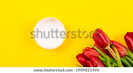 Banner with a bouquet of flowers and a jar of body or face care cream on a yellow background with copy space, text place. Holiday business card. Cosmetics store. Spa treatments. Massage cream. Mockup.