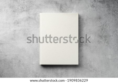 Hardcover closed blank book mockup on gray concrete background, top view, flat lay, minimalism  Royalty-Free Stock Photo #1909836229