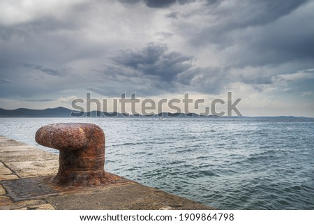 Single, old and rusty mooring bollard on the pier with a view on Adriatic Sea and dramatic sky in Zadar bay, Croatia Royalty-Free Stock Photo #1909864798