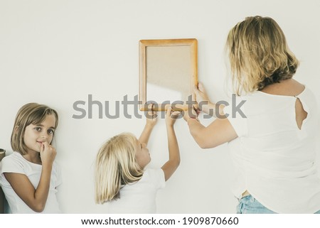 Lovely girl putting frame on white wall with help of mom. Cute daughter hanging blank picture. Her sister standing near and looking away. Family decorating room. Relocation and moving day concept