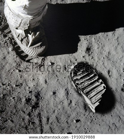 An illustration of Astronaut's boot print on moon (lunar) surface. Elements of this image furnished by NASA. Royalty-Free Stock Photo #1910029888