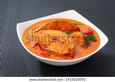 Fish curry_Seer fish curry ,traditional Indian fish curry ,kerala special dish using coconut ,arranged in a white bowl garnished with curry leaves  on black textured  background, isolated. Royalty-Free Stock Photo #1910030092