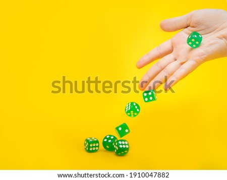 A lot of green dice fall from the hand on a yellow background with space for text: board games, selective focus on the hand, a photo in motion