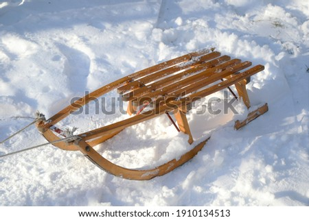 Old wooden sledge in the fresh snow. Winter sports, vacations and games concept concept. Sled with rope