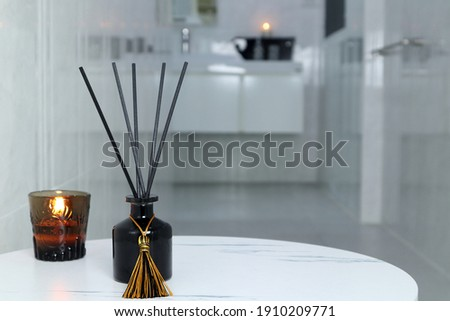 luxury glass aroma scent reed diffuser bottle and scented candle are used as air freshener in the nice white toilet bahtroom to creat relax , cozy and clean ambient Royalty-Free Stock Photo #1910209771