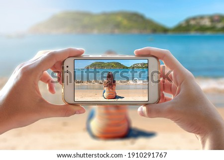 Woman photographing other girl sitting in the beach. She is using to take a photo the camera of a smartphone. A person photographing her friend with a cell phone.