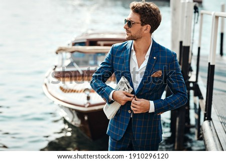 Young handsome man in classic suit over the blurred lake buttoning his jacket Royalty-Free Stock Photo #1910296120