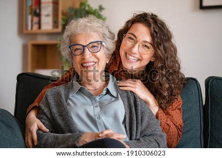 Portrait of old grandma and adult granddaughter hugging with love on sofa while looking at camera. Happy young woman with eyeglasses hugging from behind older grandma with spectacles generation family Royalty-Free Stock Photo #1910306023