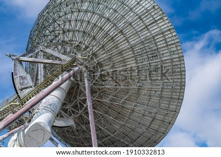 Huge satellite antenna dish for communication and signal reception out of the planet Earth. Observatory searching for radio signal in space at sunset. Royalty-Free Stock Photo #1910332813