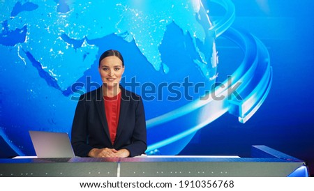 Live News Studio with Professional Female Newscaster Reporting on the Events of the Day. Broadcasting Channel with Presenter, Anchor Smiling on Camera. Mock-up TV Newsroom Set. Royalty-Free Stock Photo #1910356768