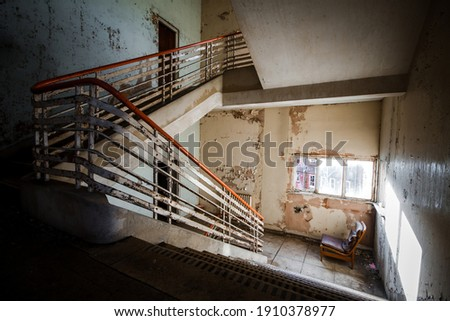 Abandoned building creepy dark moody staircase in dilapidated run down old deserted hospital school ruin with a single empty chair indoors on stairs landing no one there Royalty-Free Stock Photo #1910378977