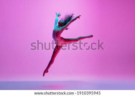 Flying, freedom. Young and graceful ballet dancer on pink studio background in neon light. Art, motion, action, flexibility, inspiration concept. Flexible caucasian ballet dancer, moves in glow. Royalty-Free Stock Photo #1910395945