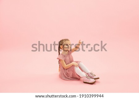Sitting, pointing. Childhood and dream about big and famous future. Pretty longhair girl on coral pink studio background. Childhood, dreams, imagination, education, facial expression, emotions concept Royalty-Free Stock Photo #1910399944