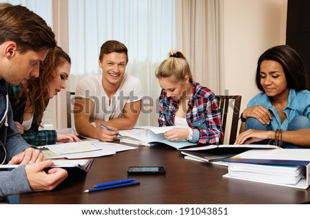 Multi ethnic group of students preparing for exams in home interior behind table  #191043851