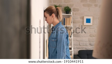 Young woman hits her head against the wall. The stressed young woman stands at her home and bangs her head against the concrete wall, condemning herself and torturing herself.  Royalty-Free Stock Photo #1910441911