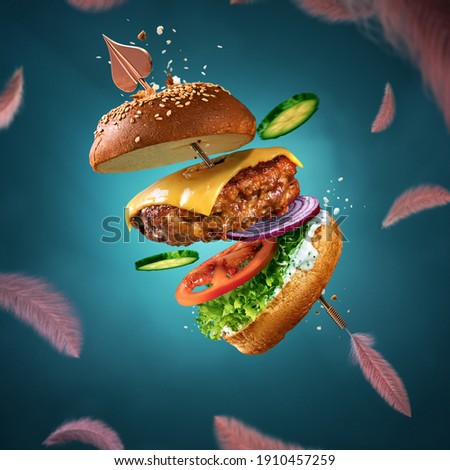 Delicious burger with flying ingredients and sauce. Valentine's day poster. Cupid's arrow pierces the burger. For the love of food. Blue background with flying feathers