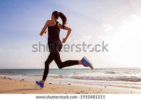 Runner on the beach at dawn.  Royalty-Free Stock Photo #1910481211