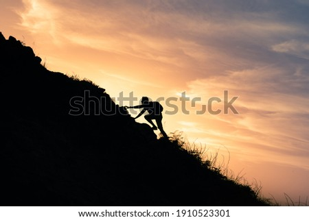 Young man climbing up to top of mountain. Self improvement and motivational goals concept.  Royalty-Free Stock Photo #1910523301