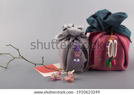 Korean traditional wrapping cloth gift box on the gray background Royalty-Free Stock Photo #1910623249
