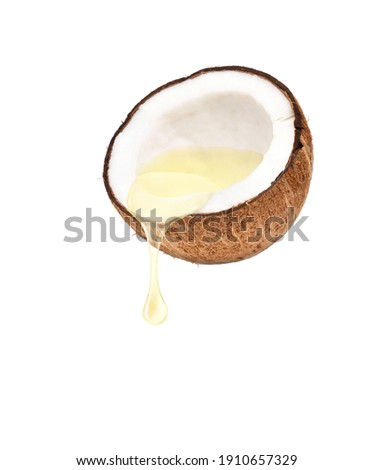 Coconut oil dripping from coconut fruits cut in half isolated on white background. Royalty-Free Stock Photo #1910657329