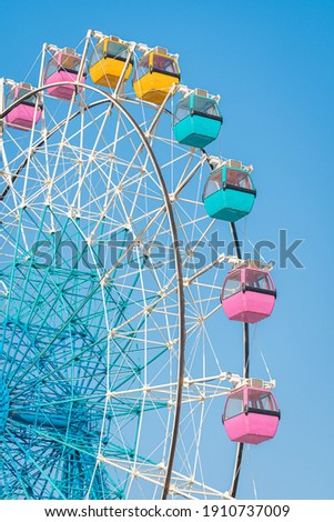 Colorful ferris wheel in an amusement park against blue sky Royalty-Free Stock Photo #1910737009