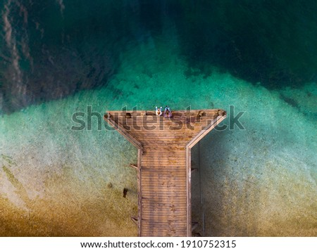 Top down aerial view. A loving couple are sitting on a wooden bridge, a pier. Sunny day, clear water, mountain lake. The concept of romance, outdoor recreation. Relationships and travel. Copy space Royalty-Free Stock Photo #1910752315