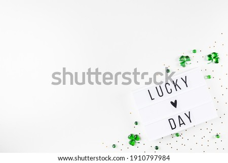 Lightbox with Saint Patricks day greeting text, shamrocks made of green hearts and stars confetti on white background Flat lay Irish holiday party card Spring 17 march lucky clover design Copy space