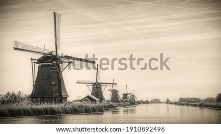 traditional dutch windmills at riverside, landscape picture in the netherlands