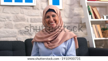Beautiful face portrait of happy mature middle-aged woman in hijab. Old lady in turban looking at camera with healthy cheerful smile.  Royalty-Free Stock Photo #1910900731