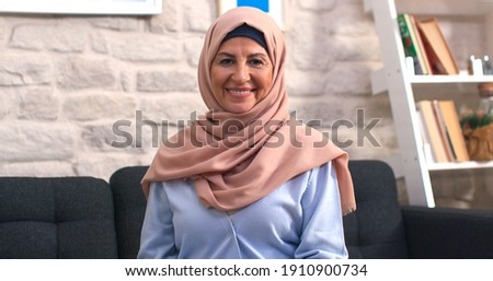 Beautiful face portrait of happy mature middle-aged woman in hijab. Old lady in turban looking at camera with healthy cheerful smile.  Royalty-Free Stock Photo #1910900734