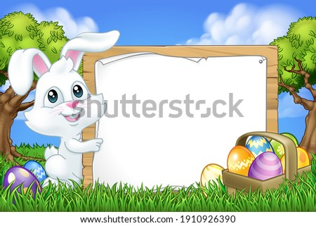 The Easter Bunny Rabbit peeking around a sign background and pointing at it in a park or field with Easter eggs.
