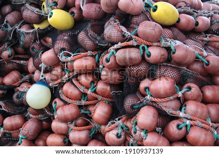 bunch of brown and yellow fishing net floats of piled up fishing nets Royalty-Free Stock Photo #1910937139